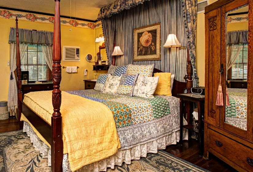 1. Yellow guest room with wood floors, colorfully covered four poster bed, and blue and white gingham window and bed valances