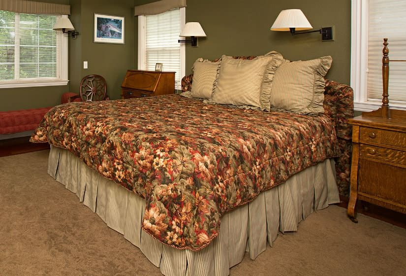 Sage green guest room with tan rug, floral covered bed, sconce lighting, wood nightstands and three windows