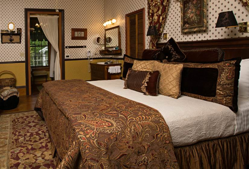 Guest room with brown paisley and gold covered bed, black trim, wood floors, area rug, and sconce bed lighting