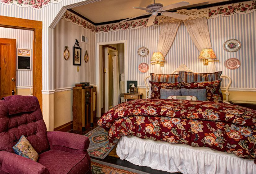 Guest room with blue and white striped wallpaper, red floral covered bed, sconce lighting over bed, and red upholstered chair