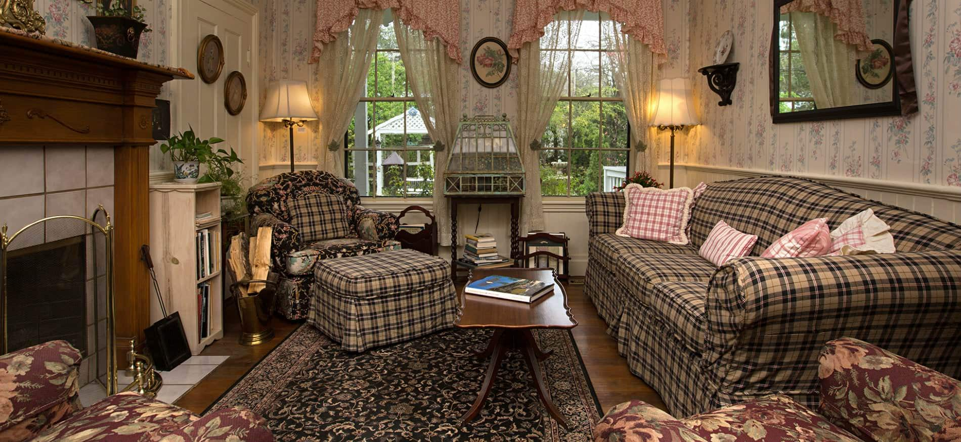 Sitting room with black and white plaid sofa and chair, coffee table, wood floors, and two windows with lace curtains