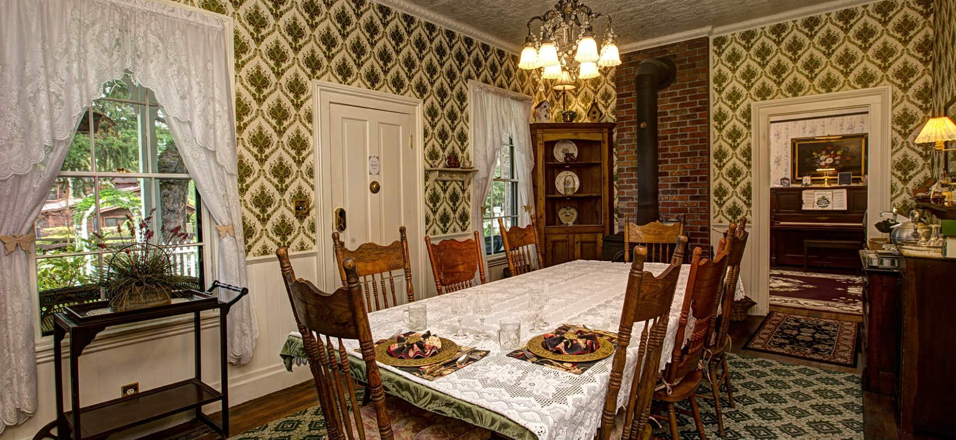 Dining room with green and white papered walls, windows with white lace curtains, and wood table with eight chairs