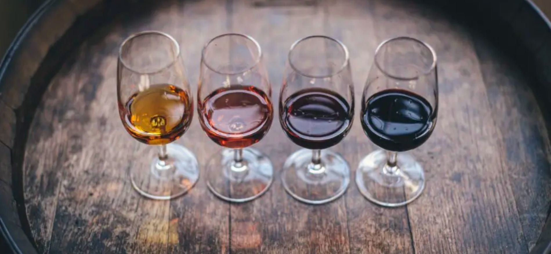 Four wine glasses on a wine barrel with different wines