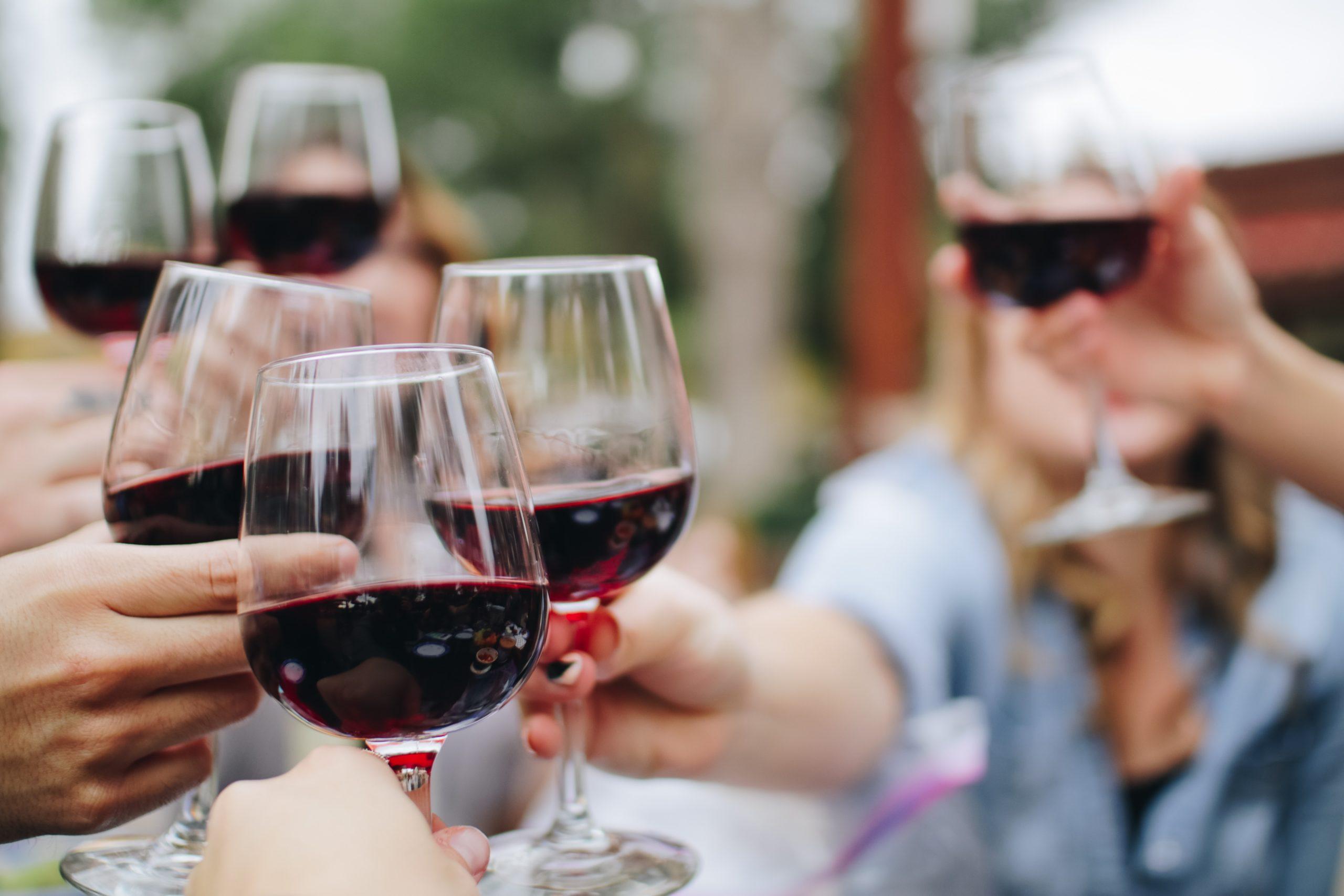 Several people raising their wine glasses in cheers