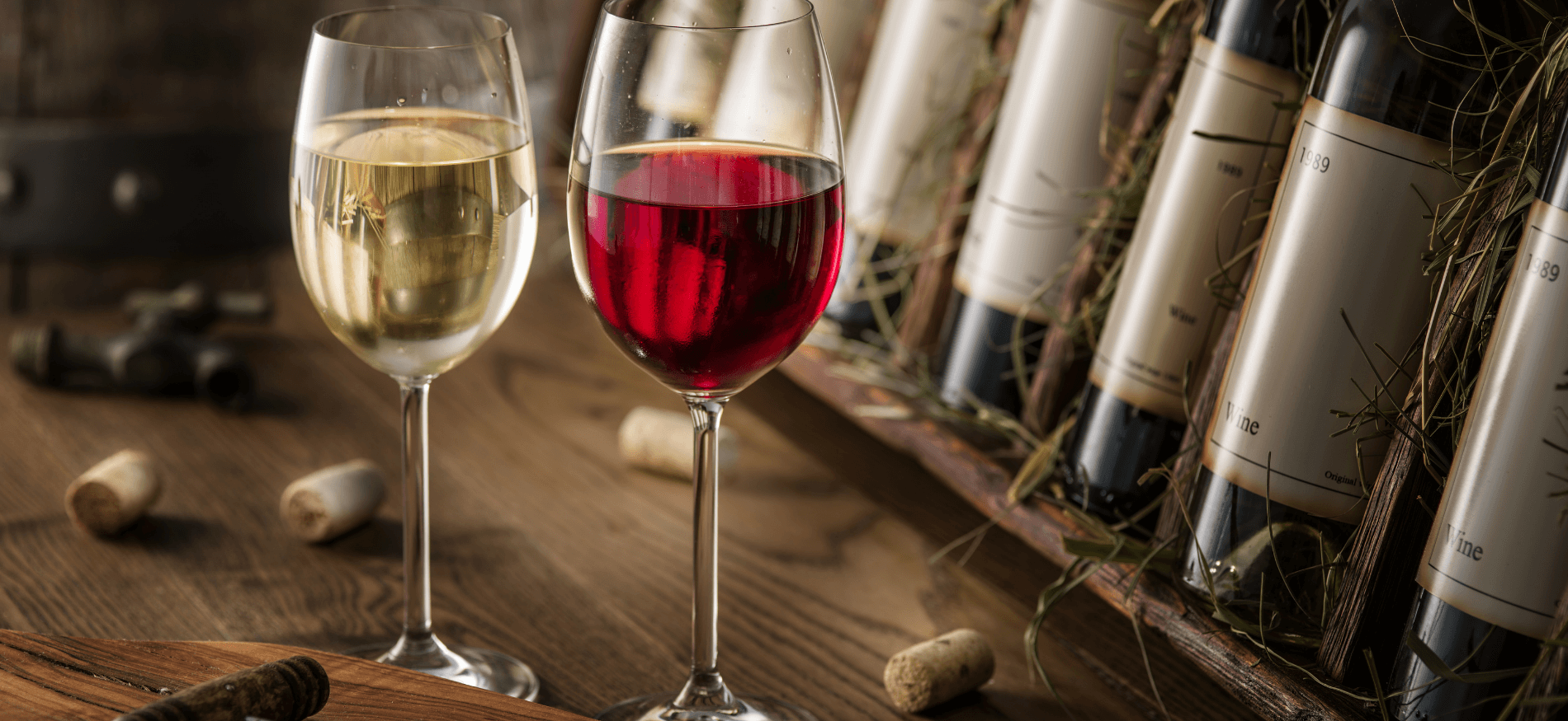 Two glasses of wine, one red and one white, in front of wine bottles.
